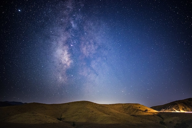밤 시간 동안 푸른 하늘 아래 갈색 산 무료 사진