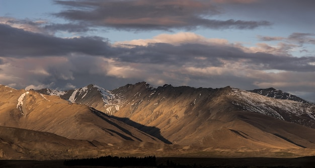 Brown mountains with light and shadow and dramatic sunset clouds on the sky scene in new zealand