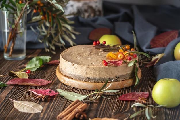 Коричневый муссовый торт, украшенный осенними листьями и ягодами