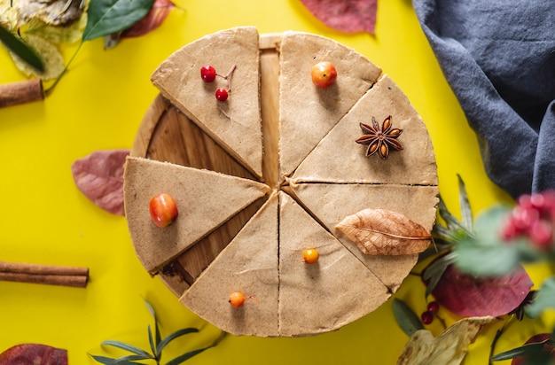 最小限の秋のシンボルで飾られた茶色のムースケーキ