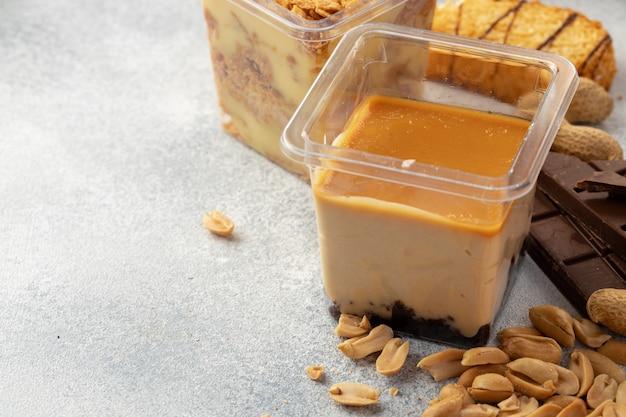 灰色の表面にあるプラスチック製の透明な箱に入った茶色のムースクリームデザート