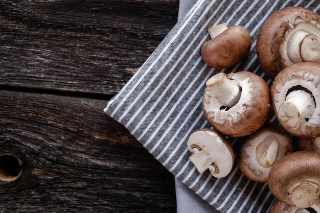 Brown mushrooms on old dark wooden background