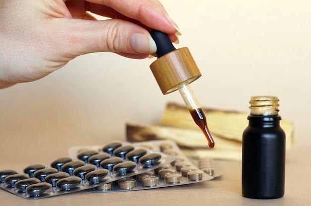 Medicina naturale marrone in una piccola bottiglia con una pipetta