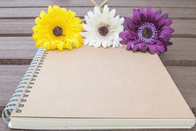 Brown notebook with colorful faked flower on blurred old wood table textured background