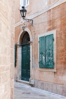 Коричневое старое здание с зелеными ставнями и старым фонарем