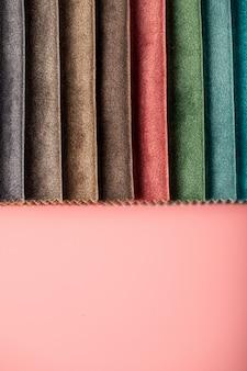 Tessuti in pelle sartoriale di colore marrone e arancione nel catalogo sulla parete rosa