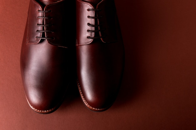 Brown oxford shoes on red . close up. top view.
