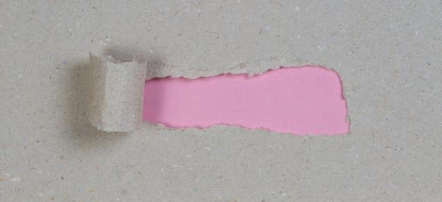 コピースペースのあるピンクの壁を明らかにするために引き裂かれた茶色のパッケージ紙