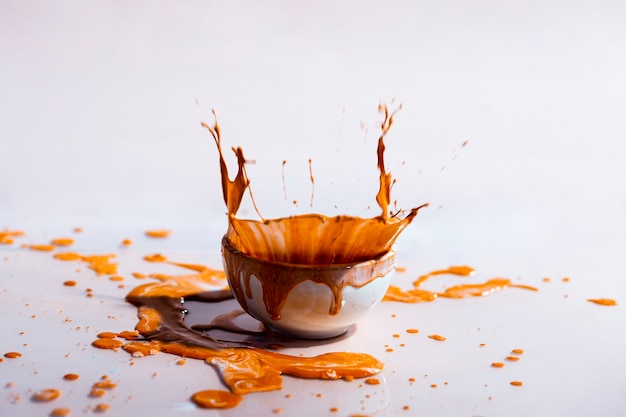 Brown paint splash and cup abstract background