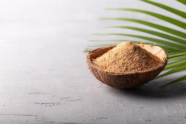 Коричневая пальма или кокосовый сахар на сером