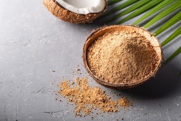 Коричневый пальмовый сахар в шаре кокоса на серой конкретной предпосылке.