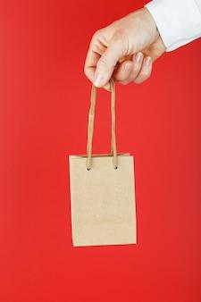 Коричневый бумажный мешок на расстоянии вытянутой руки, на красном фоне.