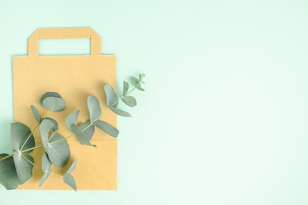 緑の背景に茶色の紙袋。ゼロウェイスト、環境にやさしい。