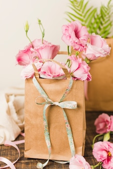 Brown paper bag with fresh pink eustoma flower on wooden table
