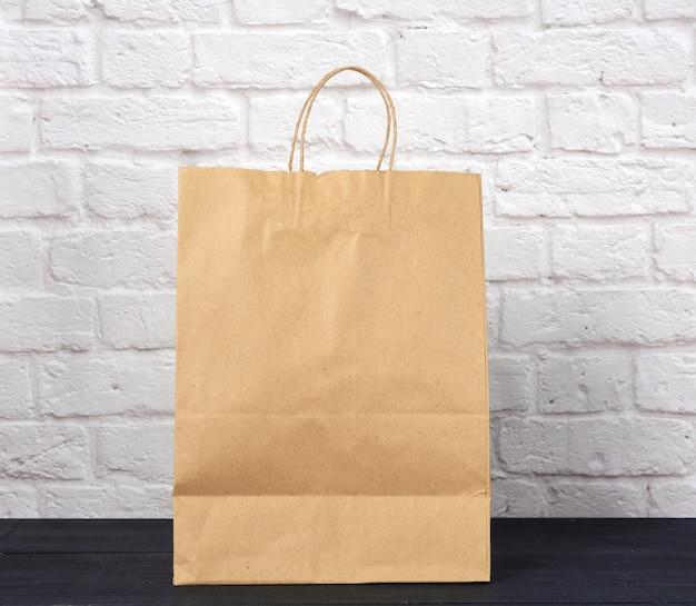 Коричневый бумажный пакет с ручками на белой кирпичной стене, экологический материал, нулевые отходы