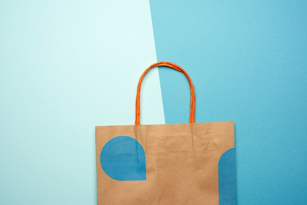 Brown paper bag with handles for shopping on a blue background, flat lay