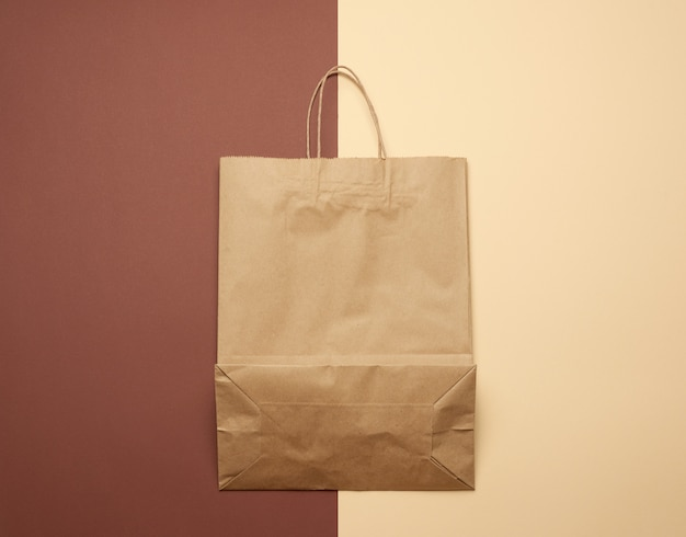 Brown paper bag with handles for shopping on a brown background