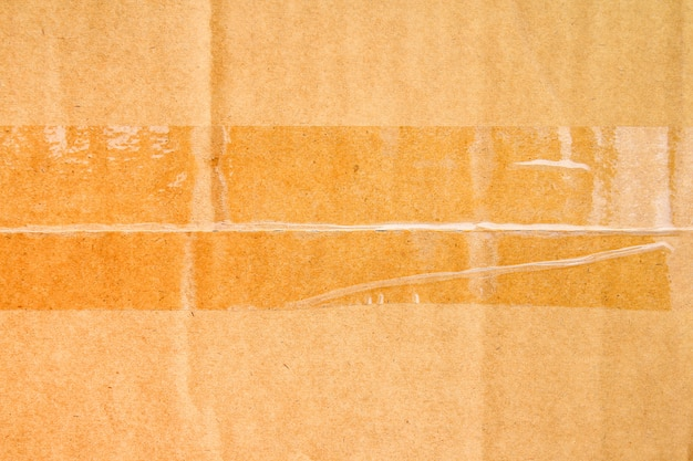 Brown paper box or corrugated cardboard sheet with tape texture