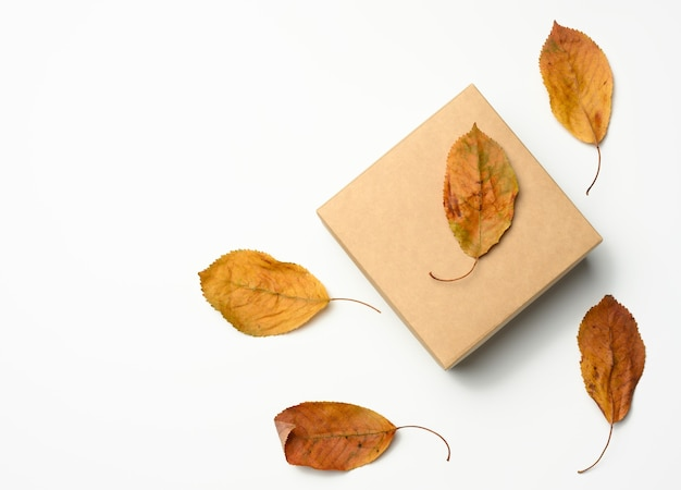 Brown paper box and dry golden cherry leaves, top view