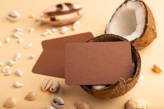 오렌지 파스텔 배경에 코코넛과 조개 껍질이 있는 갈색 종이 명함. 측면보기,