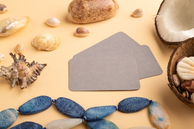 Визитная карточка коричневой бумаги с кокосом, ракушками, галькой, бусинами на оранжевом пастельном фоне.
