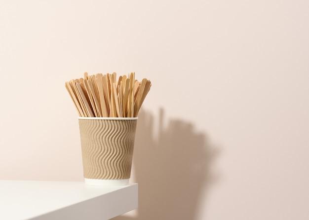 Картонные чашки коричневой бумаги и деревянные палочки для перемешивания на белом столе, бежевом фоне. экологичная посуда, без отходов