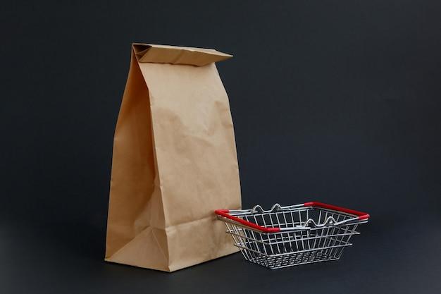 黒の背景と小さな食料品バスケットで買い物をするための茶色のペーパークラフトバッグ