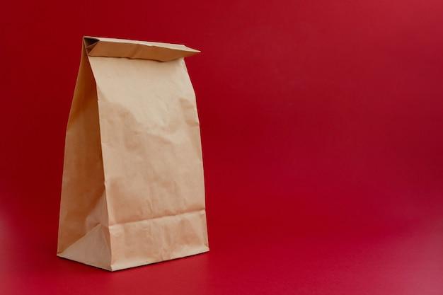 赤い背景で買い物をするための茶色のペーパークラフトバッグ