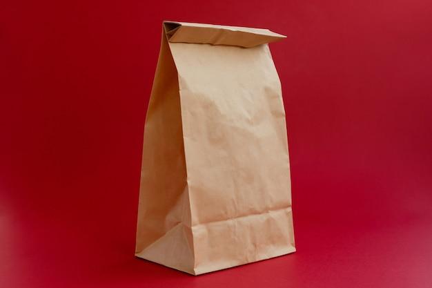 빨간색 배경에 쇼핑 갈색 종이 공예 가방