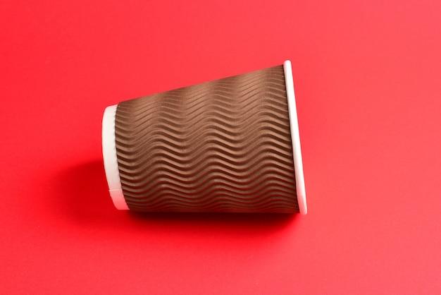 赤の背景に茶色の紙コップ。スペースをコピーします。