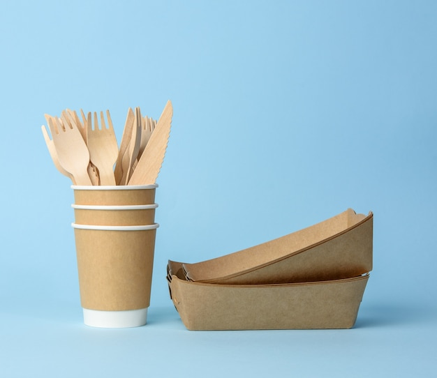 Brown paper cup, plates on a blue surface. plastic rejection concept, zero waste