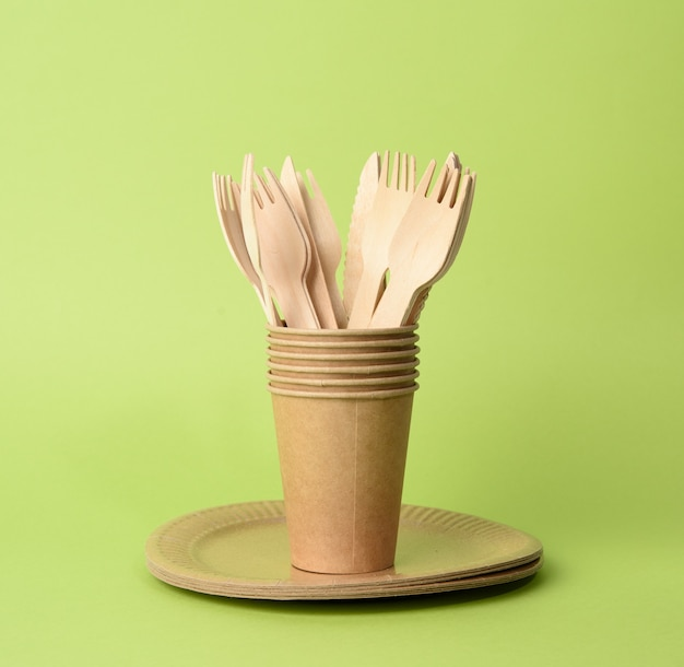 Brown paper cup, plates on a green background. plastic rejection concept, zero waste, close up