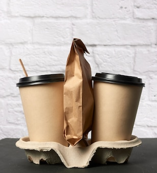 Brown paper disposable cups with a plastic lid standing in the tray