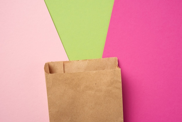 Одноразовый пищевой мешок из коричневой бумаги на розовом фоне