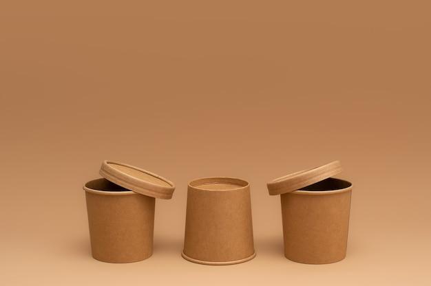 Коричневая бумага одноразовые суповые чашки на бежевом фоне. концепция нулевых отходов. картонная посуда