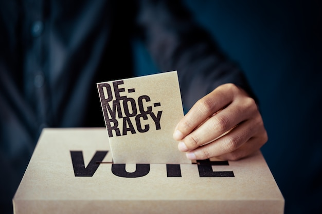 Brown paper insert in vote box, democracy concept, retro tone