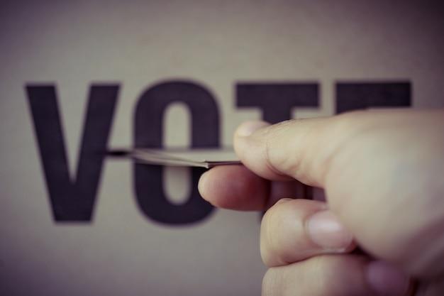 Brown paper insert in vote box, democracy concept, retro tone