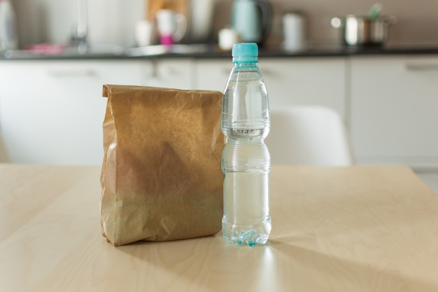 Brown paper lunch bag and bottle of water on wooden table over kitchen background.