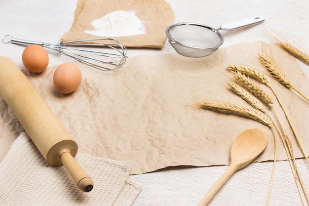 Коричневая бумага на столе. сито, венчик и скалка. бумага, мука, яйца и колоски пшеницы. белый фон. вид сверху
