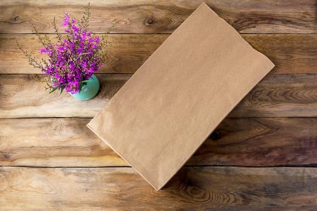 Макет сумки для покупок из коричневой бумаги с фиолетовыми полевыми цветами
