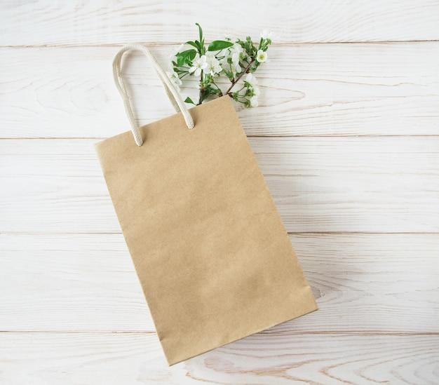 Коричневая бумажная хозяйственная сумка с ручками и цветущими цветами внутри на белом деревянном фоне