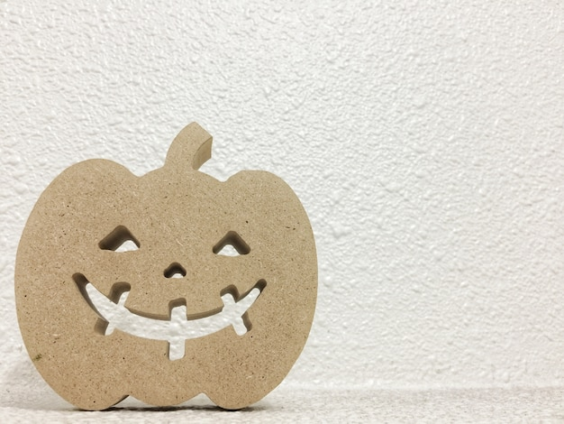 A brown paper smile ghost pumpkin shape on white cement copy space wall background.