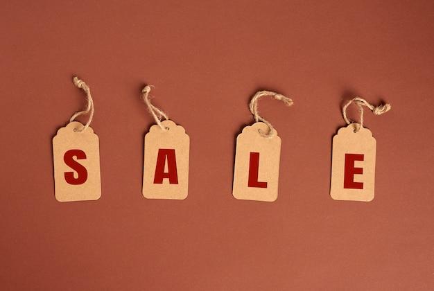 Оберточные бумажные бирки с надписью продажа на коричневом фоне, концепция сезонных скидок, вид сверху