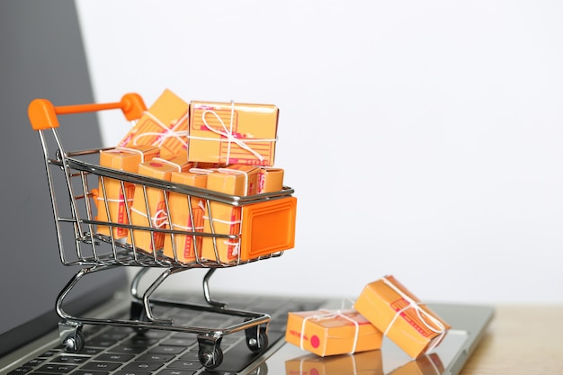 Brown parcel box and model miniature shopping cart on computer keyboard