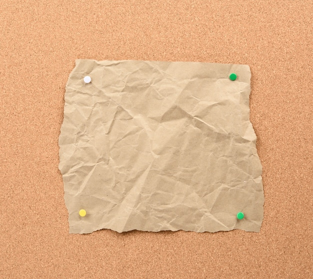 Brown piece of torn paper pinned with iron buttons on a brown cork board