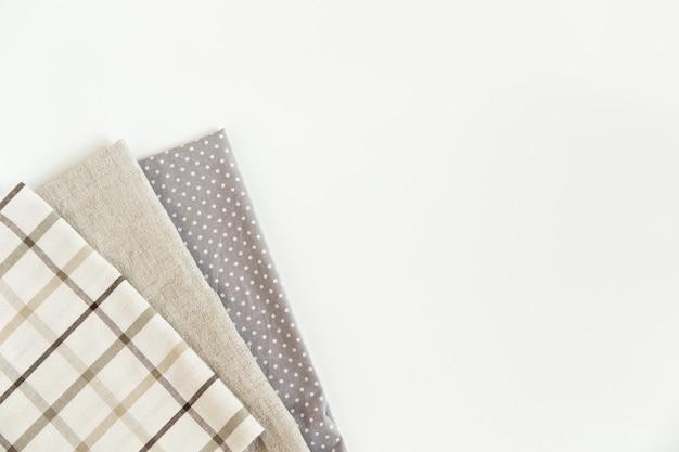 茶色の格子縞のテーブルクロスと灰色のナプキンの粗い布タオルと上面図に点在