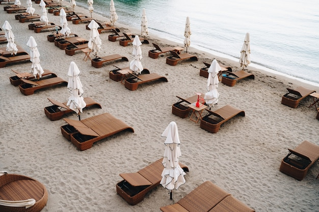 모래 해변에 우산이 있는 갈색 플라스틱 고리버들 의자