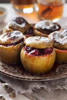 Brown plate of baked apples with cranberries