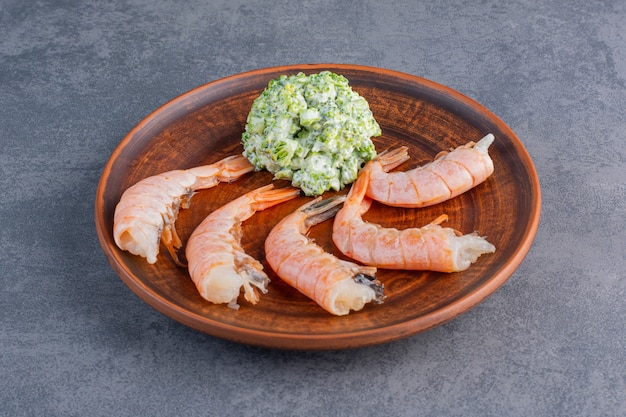 A brown plate of delicious shrimps on a stone surface