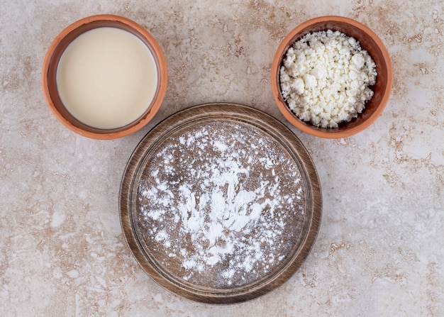 A brown plate of flour and a clay bowl of cottage cheese